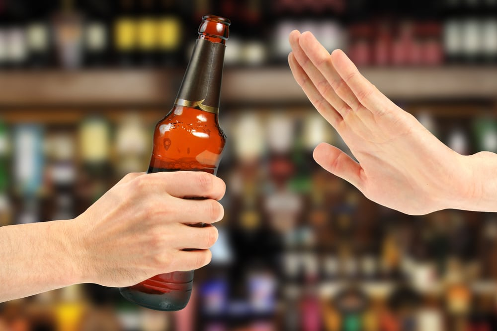 Photo of a hand gesturing NO to a beer