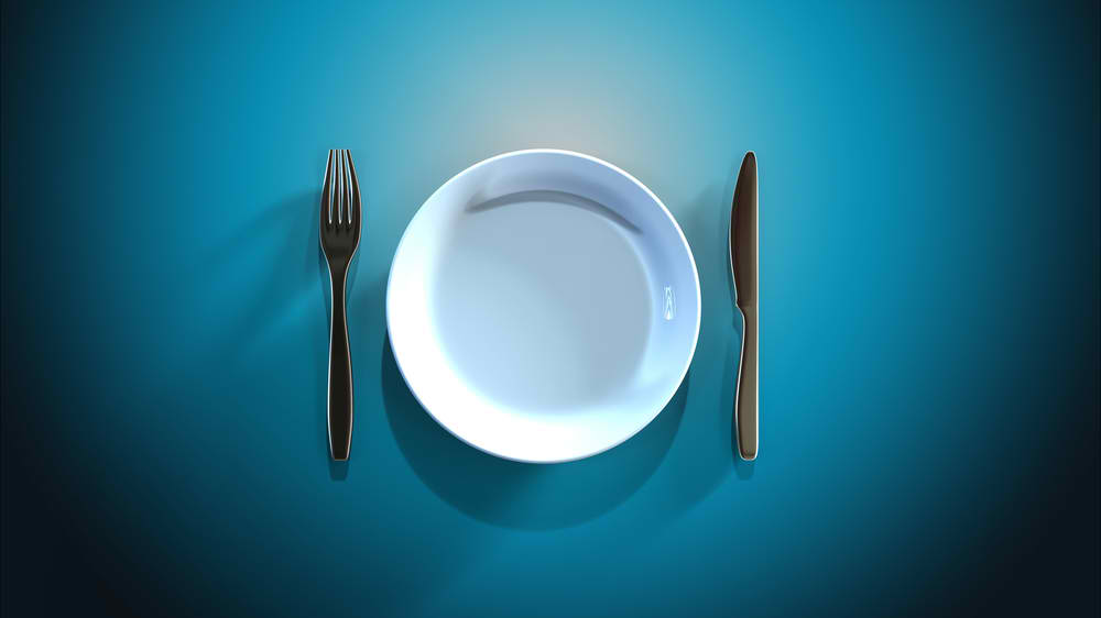 A photo of a blank plate with fork and knife at the sides. A plate for intermittent fasters maybe?